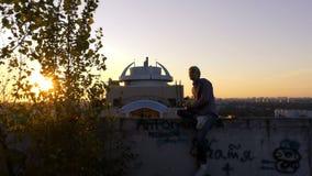 4k - Um homem encontra o alvorecer no telhado da casa que escuta a música video estoque