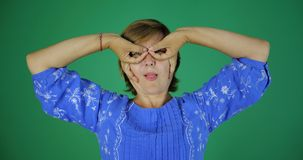 4k - Uma mulher adulta que sorri e que faz um gesto dos dedos no formulário fotos de stock royalty free