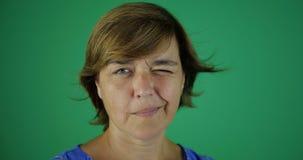 4k - Uma senhora séria com um vento em seus piscadelas e sorrisos do cabelo - o verde scren video estoque