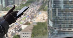 4k, umano facendo uso di uno smartphone con la costruzione di affari & il fondo di traffico urbano archivi video