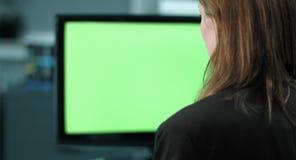 4K: Un empleado de sexo femenino trabaja en una pantalla del greenkey del ordenador almacen de metraje de vídeo