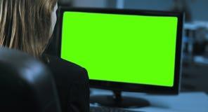 4K: Un encargado de sexo femenino joven está trabajando delante de un monitor en su oficina almacen de video