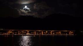 4K un train élevé voyage dans le bridt au-dessus d'un lac pendant le nigth clips vidéos