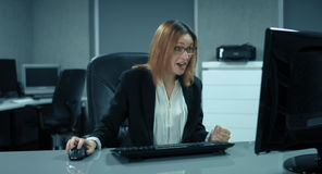 4K: Una secretaria está trabajando en un ordenador en su oficina Ella está repentinamente tan contenta como sacador