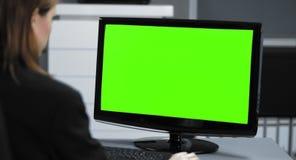 4K: Una secretaria joven está trabajando en su oficina El monitor se cierra en el verde de la croma para compositing
