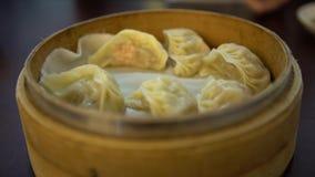 4K usando el palillo para comen las bolas de masa hervida en restaurante Alimento del chino tradicional almacen de video