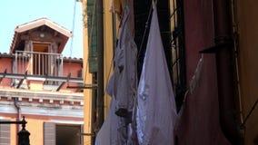 4K Vêtements accrochant sur la façade d'une maison sur une rue étroite à Venise, Italie clips vidéos