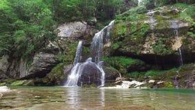 4K Vattenfall Virje i slovenska fjällängar, blått vatten och gräsplanskogen Julian Alps, Bovec område, Slovenien, Europa för reng stock video