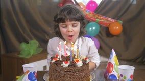 4k - Velas que soplan de la muchacha hermosa joven en una torta de cumpleaños almacen de metraje de vídeo