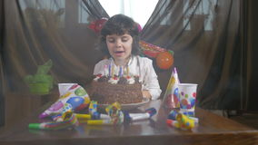 4k - Velas que soplan de la muchacha hermosa joven en una torta de cumpleaños almacen de video
