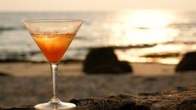 4K vetro di cocktail con le goccioline di acqua sulla spiaggia con la riflessione dorata dell'onda durante il tempo di tramonto stock footage