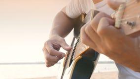 4K vicino su di un uomo giocare la chitarra acustica alla spiaggia durante il tempo del tramonto, sensibilità si rilassa archivi video