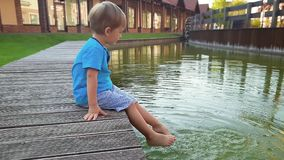 4k footage of adorable toddler boy sitting on the riverbank and dipping his feet in water. Child moving legs and