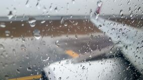 4k video through airplane window covered with rain dorplets of airplane driving on runway during heavy rain storm