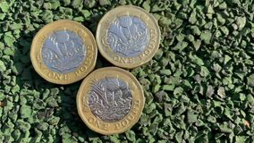4k Video British Pound Sterling Coins closeup. Pound Coins laying on the road on the sunlight. Three one pound coins. Br