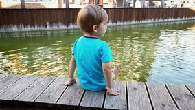 4k video of chererful smiling toddler boy sitting on the riverbank and holding feet in water of small canal at european
