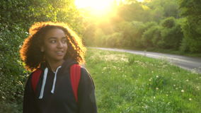 Beautiful happy mixed race African American girl teenager female young woman hiking with red backpack in the country at sunset stock video footage