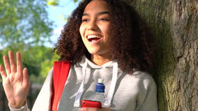 African American girl teenager leaning against a tree using cell phone stock video