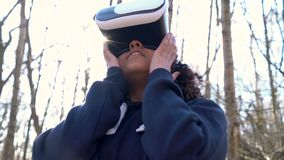 Biracial African American girl teenager female young woman using virtual reality VR headset in a forest woodland environment. 4K video clip of beautiful mixed stock video footage