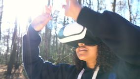 Girl teenager female young woman using virtual reality VR headset in a forest woodland environment. 4K video clip of beautiful mixed race African American girl stock video footage