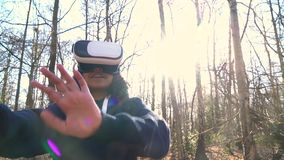 Girl teenager female young woman using virtual reality VR headset in a forest woodland environment. 4K video clip of beautiful mixed race African American girl stock footage