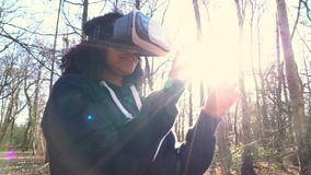 Biracial African American girl teenager female young woman using virtual reality VR headset in a forest woodland environment. 4K video clip of beautiful mixed stock video