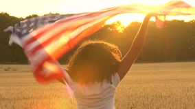 African American girl teenager female young woman holding American US Stars and Stripes flag in. 4K video clip of mixed race African American girl teenager stock footage