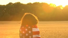 African American girl teenager female young woman holding an American USA Stars and Stripes flag in a wheat field at sunset or sun stock video