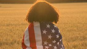 African American girl teenager female young woman holding an American USA Stars and Stripes flag in a wheat field at sunset or sun