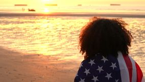 African American girl teenager female young woman wrapped in an American US Stars and Stripes flag on a beach. 4K video clip of mixed race African American girl stock video footage
