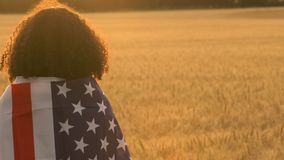 African American girl teenager female young woman wrapped in an American US Stars and Stripes flag. 4K video clip of mixed race African American girl teenager stock footage