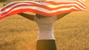 4K video clip of mixed race African American girl teenager female young woman wrapped in an American US Stars and Stripes flag in. A wheat field at sunset or stock video