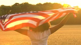 African American girl teenager female young woman holding an American USA Stars and Stripes flag stock video footage