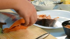 4k video. Cook cuts salmon steaks. stock video footage