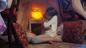 4k video of cute girl sitting in tent at bedroom and hugging big teddy bear stock video footage
