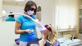 4k video die van mooie blondevrouw als tandartsvoorzitter tijdens tanden het witten liggen stock video