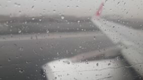 4k video of flowing rain water streams on the airplane window during takeoff from wet runway in storm