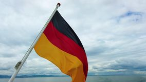4K video of Germany flag flying in the wind on the ship. In the background is blue sky. There is sunny day stock footage