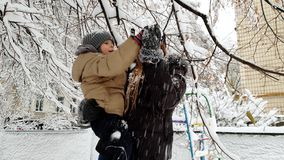 4k video of happy laughing toddler boy with young mother standing under tree covered in snow and shaking its branches stock footage