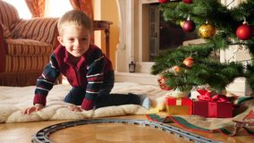 4k footage of happy smiling little boy lying on floor at living room decorated for Christmas and playing with toy train stock video