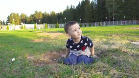 Sitting on the ground fearful child. 4k video of happy three year old boy stock footage