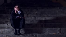 4K video lateral panning 24 fps of young desperate businessman in suit and tie suffering stress drepression sitting on staircase. 4K video lateral panning 24 fps stock footage