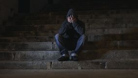 4K video lateral panning 24 fps of young desperate wasted man in hood suffering stress drepression sitting miserable on staircase stock video footage
