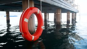 4k footage of life saving red buoy or ring hanging on wooden pier at sea beach. 4k video of life saving red buoy or ring hanging on wooden pier at sea beach stock footage