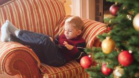 4k video of little boy lying on sofa at living room and using tablet computer. Child having fun on winter holidays and stock video footage