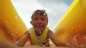 4K Video: Little boy slides fast by the inflatable slide into the water pool with active camera in front of his face stock video