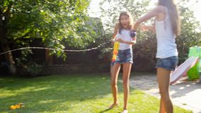 4k video of little toddler boy filling toy gun with water and splashing in two elder sister at hot sunny day stock video footage
