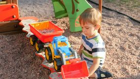 4k video of little toddler boy playing in sandbox and loading gravel and sand in toy trailer with plastic shovel. 4k footage of little toddler boy playing in stock video