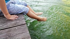 4k footage of little toddler boy sitting on riverbank and splashing water with his feet. Child dipping legs in river