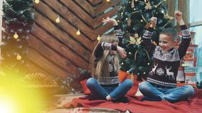 4k video with llittle boy and girl laughing, raising their hands up, looking at the mystery light near Christmas tree.